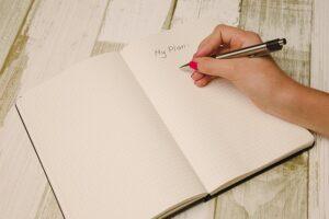 Tekstforfatteren planlægger sin tekst i en notesblok, så han kan skrive gode tekster